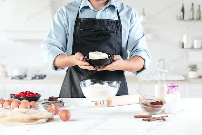 A cook with eggs on a rustic kitchen against the background of men's hands