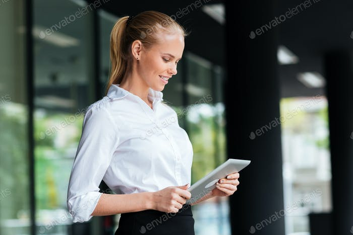 Businesswoman using digital tablet while standing at the glass railing