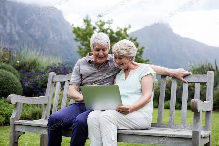 Senior couple sitting on bench and using laptop