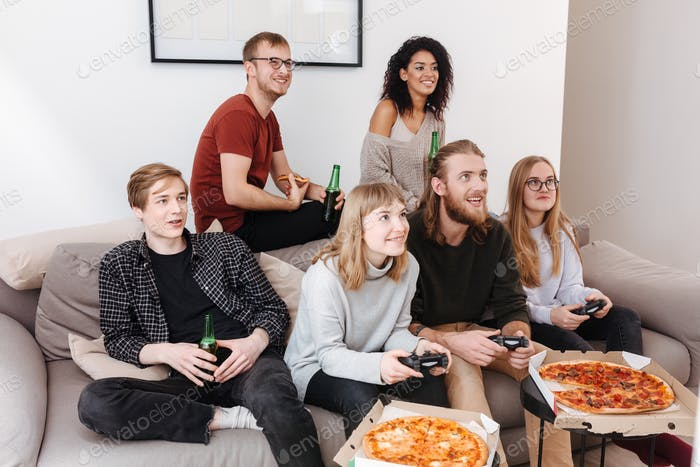Friends sitting on sofa spending time together playing video games, eating pizza and drinking beer