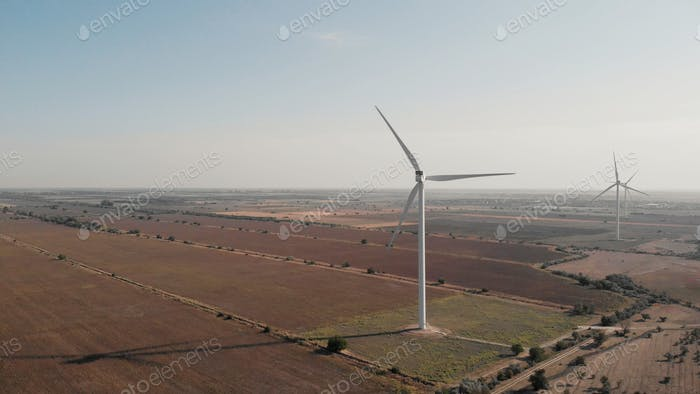 Wind turbines and agricultural fields on summer day.