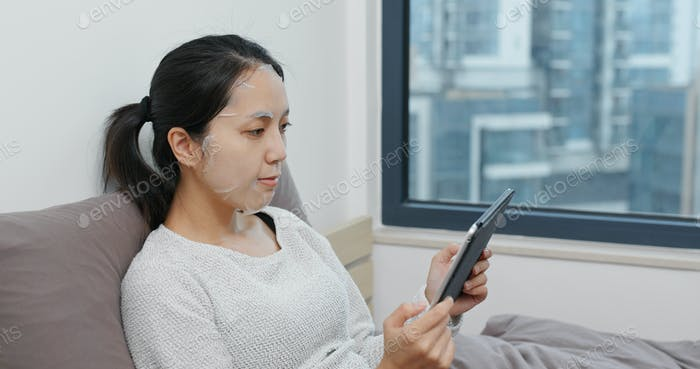 Woman apply paper mask and use of tablet computer on bed