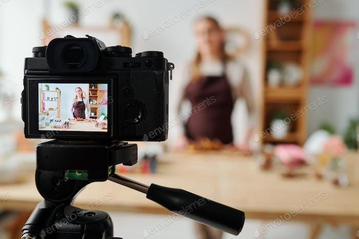 Contemporary girl on display of home camera recording soap making master class