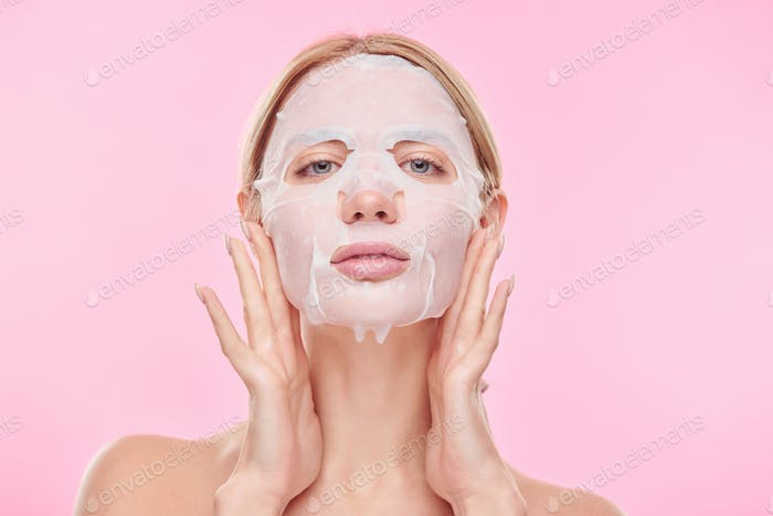 Young woman putting refreshening textile mask on face while taking care of skin
