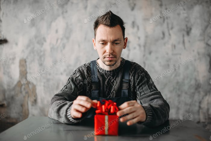 Autist man sitting against gift in wrapping paper