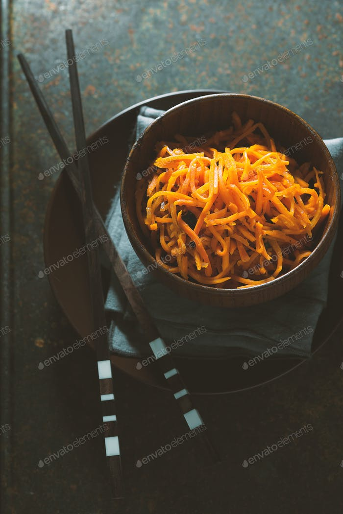 Karotten in Koreanisch und Gewürze in einer Schüssel auf Holzbrettern