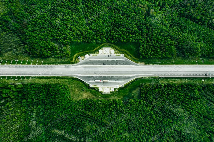 Aerial view of Toll Road Highway with parking in green Forest.
