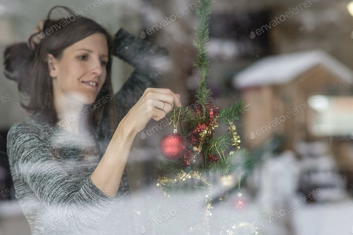 Woman putting up Christmas decorations at home