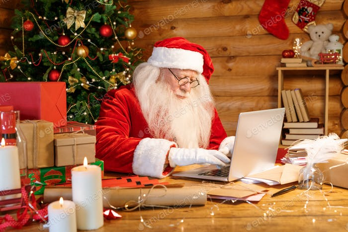 Santa Claus sitting by laptop while looking through xmas wishes in e-mail