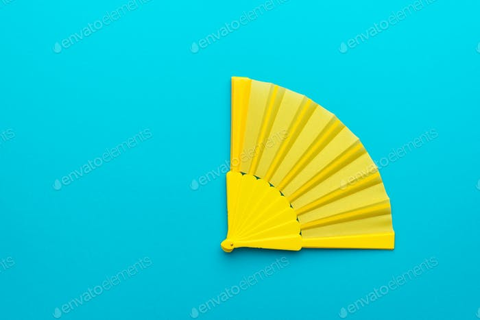 Minimalist Photo Of Yellow Hand Fan On Turquoise Blue Background With Copy Space
