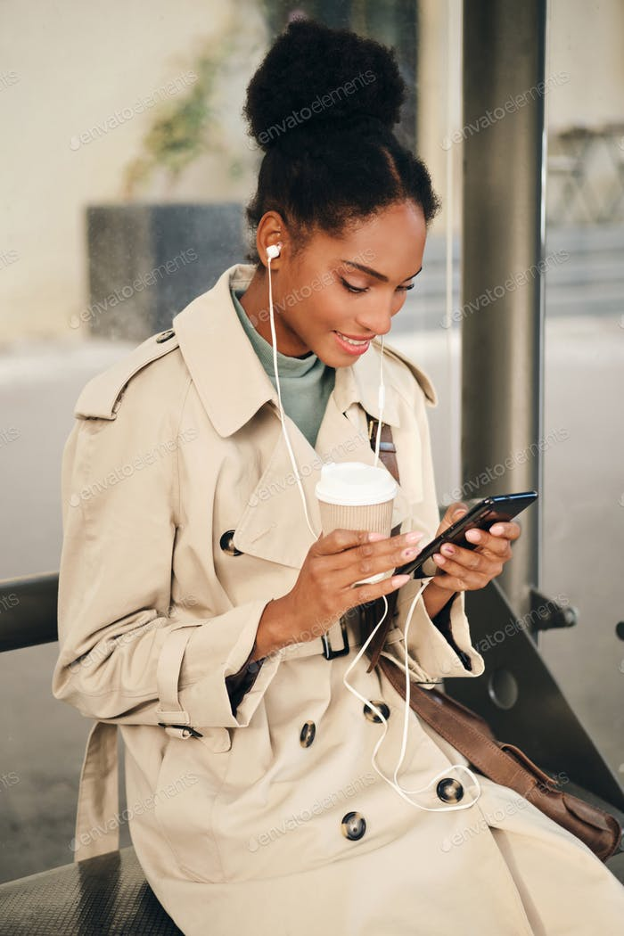 African American girl in stylish trench coat and earphones happily using cellphone at bus stop