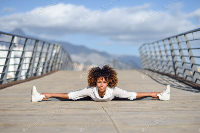 Young black woman doing stretching after running outdoors