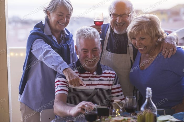 Adults senior caucasian friends have fun taking and looking piucrures on smart phone