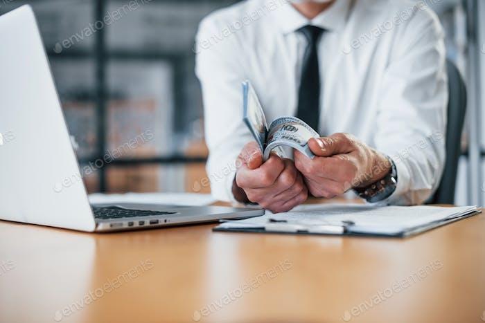 Nahaufnahme eines Geschäftsmannes, der Geld im Büro in Händen hält