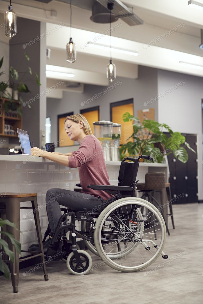 Businesswoman In Wheelchair Working On Laptop In Kitchen Area Of Busy Modern Office