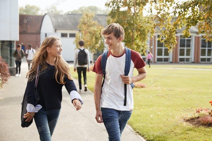 Teenage Students Walking Around College Campus Together