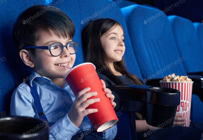 Happy boy drinking aerated sweet water and watching movie