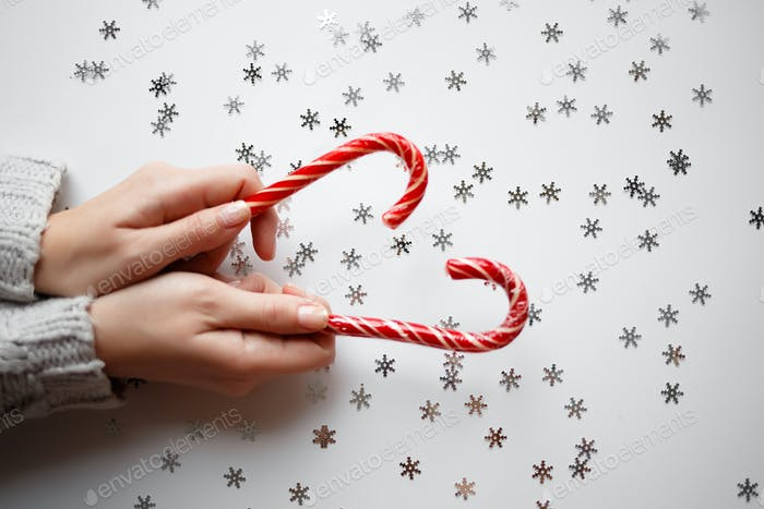 hands hold christmas lollipops on white background. selective focus
