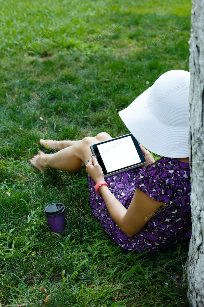 Woman on grass with tablet