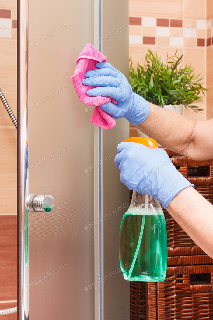 Hand of senior woman cleaning glass shower using microfiber cloth and detergent