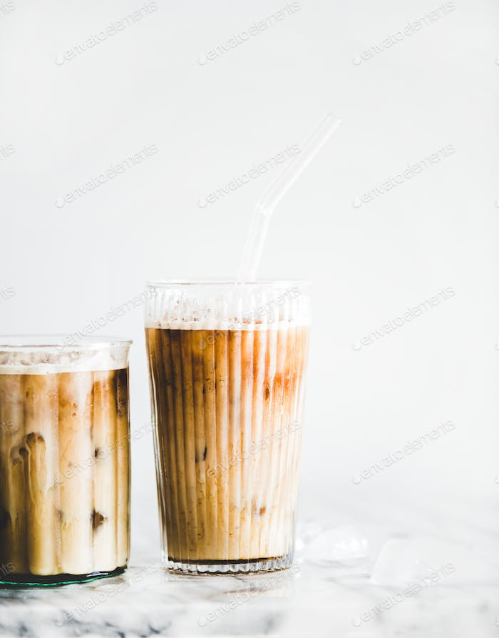 Homemade iced latte coffee in glasses on marble table
