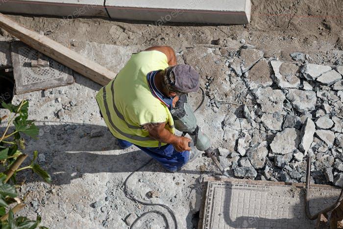 Construction worker with jackhammer drilling concrete on sidewalk