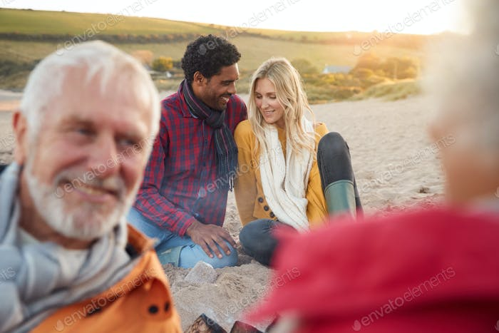 Loving Couple Relaxing By Fire With Senior Parents On Winter Beach Vacation