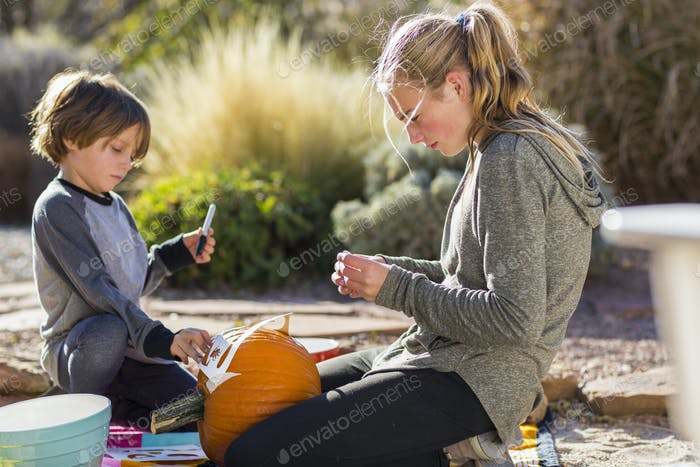 A teenage girl and a boy carving pumpkins at Halloween.