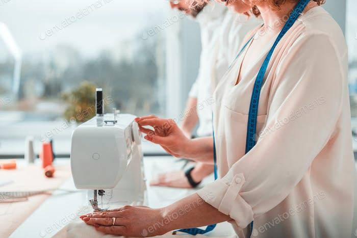 Professional dressmaker woman sews clothes on sewing machine at fashion design workshop