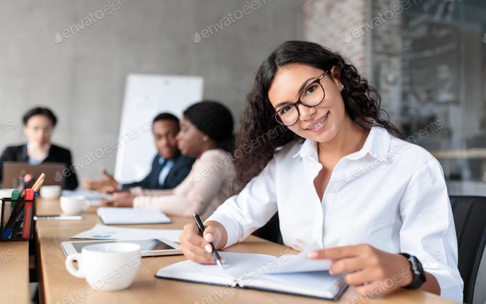 Cheerful Latin Businesswoman At Corporate Meeting Posing Sitting In Office