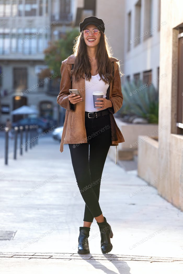 young woman looking to sideways while using her mobile phone and holding a coffee in the street.