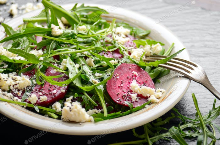 Clay dish with beetroot arugula and feta cheese salad on slate s