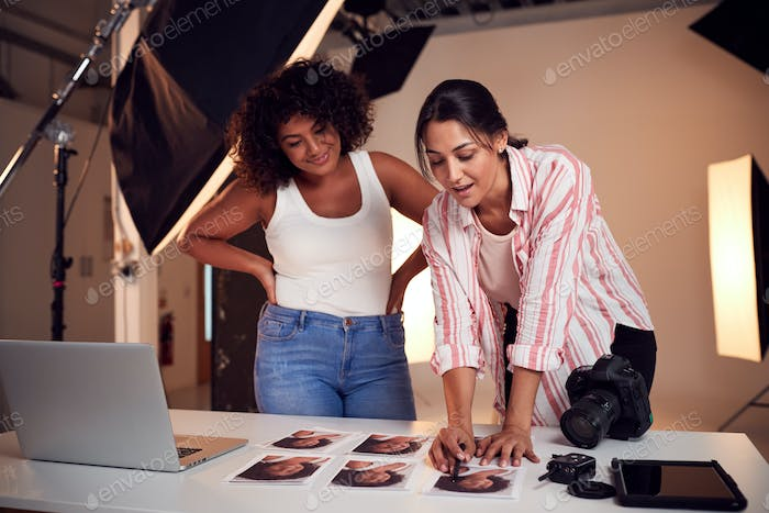 Photographer With Female Client Editing Images From Portrait Photo Shoot In Studio