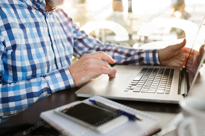 Unrecognizable senior businessman working on laptop in cafe