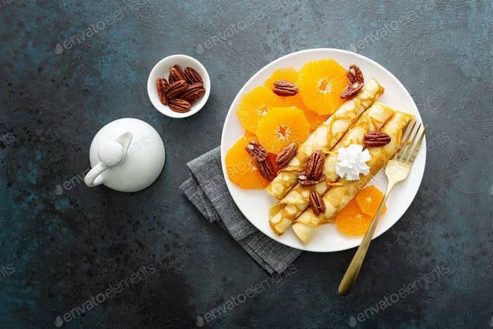 Crepes, thin pancakes with fresh tangerine slices, pecan nuts, syrup and whipped cream