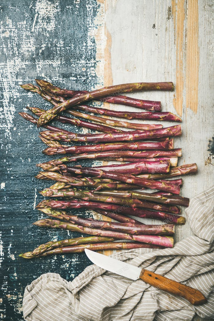 Fresh purple asparagus over rustic wooden background, vertical composition