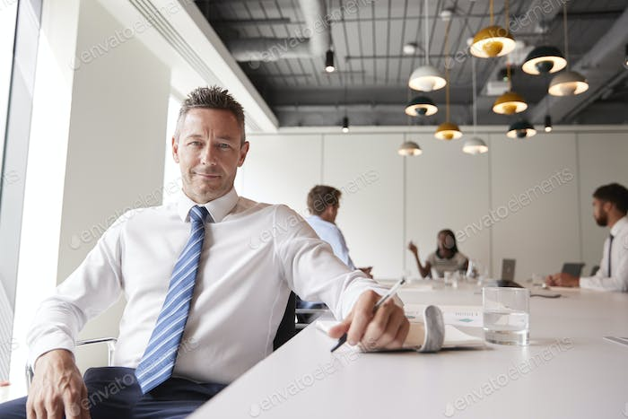 Portrait Of Mature Businessman Sitting In Modern Boardroom With Colleagues Meeting