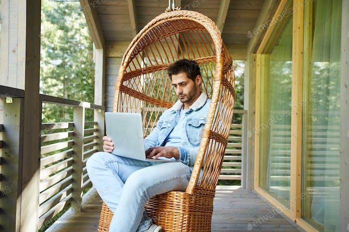 Busy freelancer browsing Internet on balcony