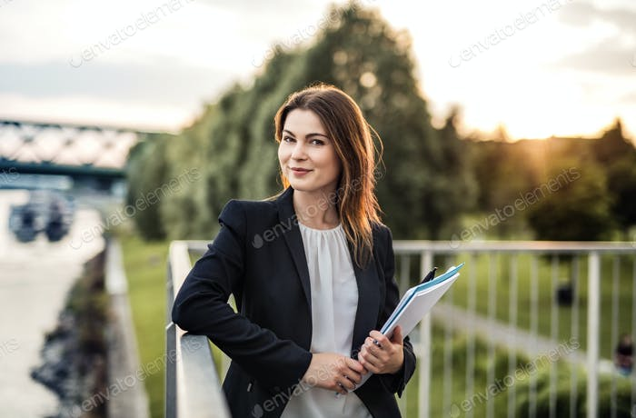 A young businesswoman standing on the river promenade at sunset.