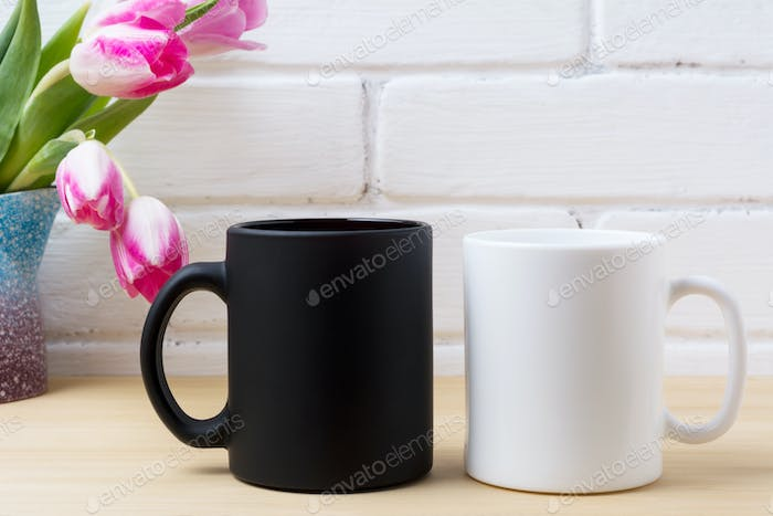 Black coffee mug and white cappuccino cup mockup with pink tulip