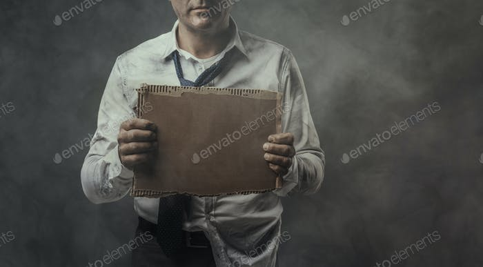 Broke jobless businessman holding a cardboard sign