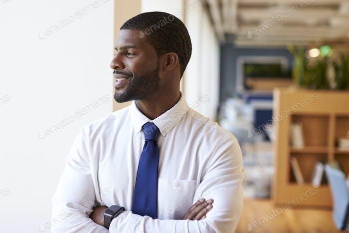 Businessman Wearing Smart Watch In Modern Office Standing By Window