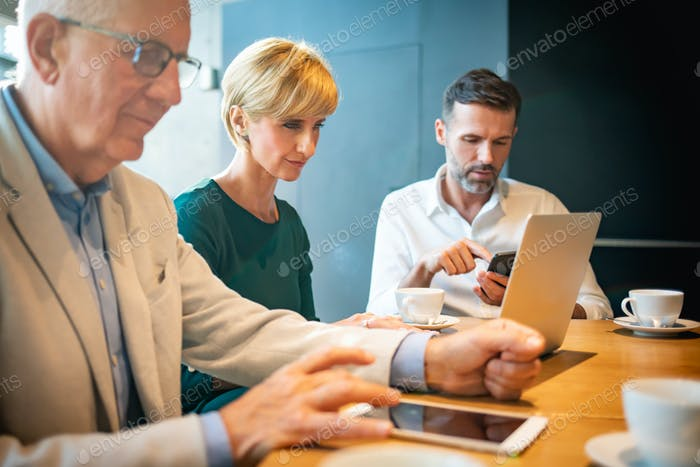 Group of business people using electronic devices in cafe