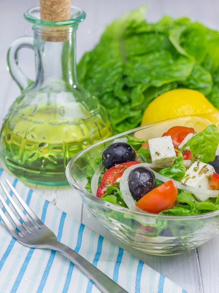 Griechischer Salat in einer Glasschüssel auf Holztisch