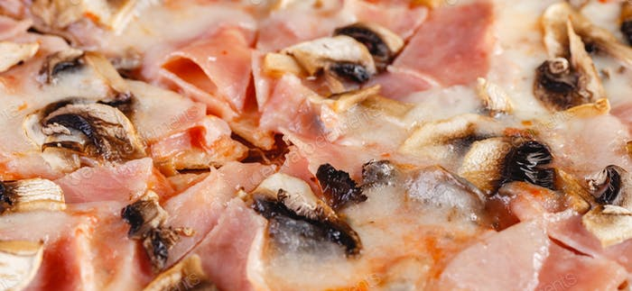 Pizza with ham and mushrooms on wooden board on dark background. Close-up