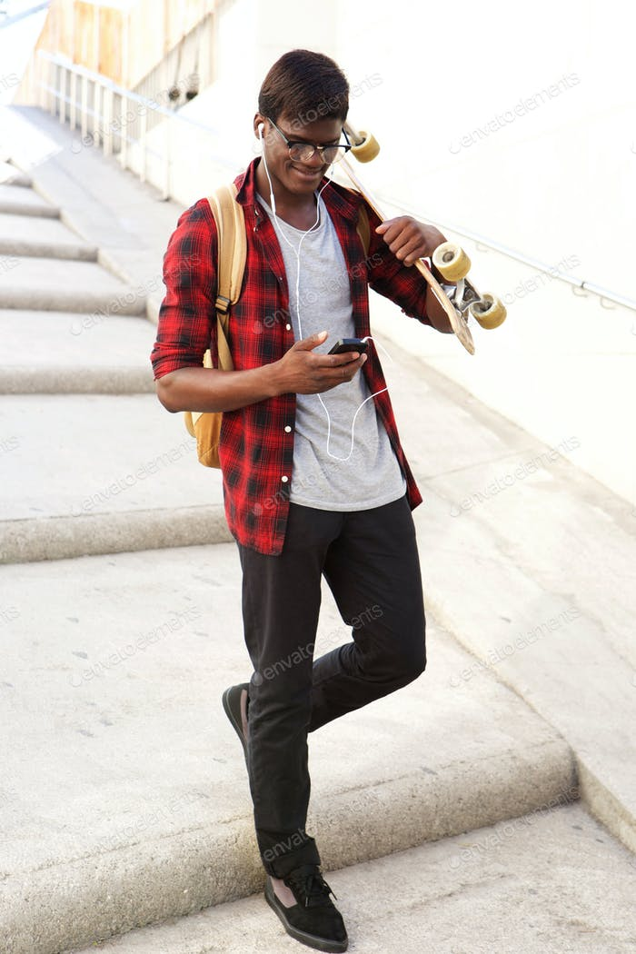 Happy african student walking down the steps with skateboard looking at cell phone