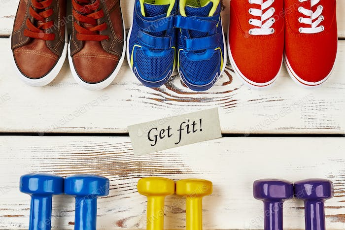 Sneakers, dumbbells and motivation card