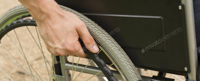 Man's hand leaned on the wheel of wheelchair