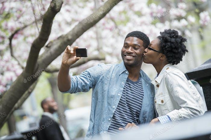 Eine Frau, die einen Mann küsst und ein Foto mit einem Handheld-Handy macht.