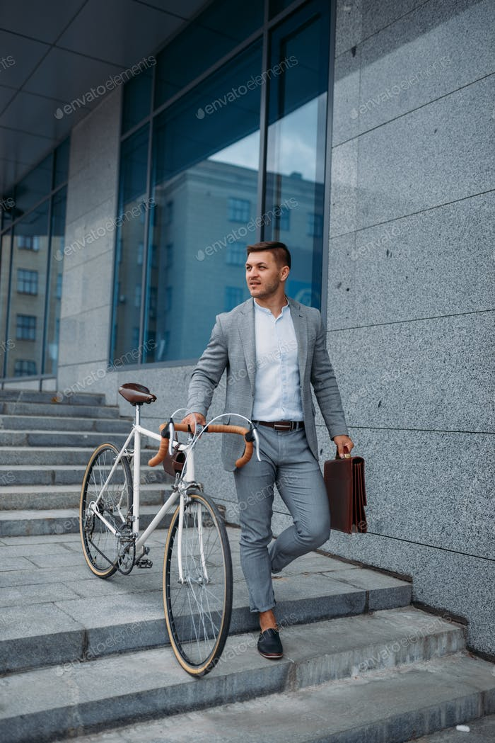 Businessman with bicycle comes down the stairs